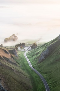 1242x2688 Road Betweeb Grassy Mountains