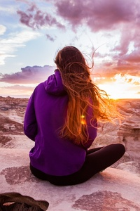 Woman In Hoodie Sitting On Rock Watching Nature