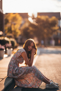 320x480 Woman In White And Brown Floral Dress Sitting On Gray Concrete Road During Daytime 5k