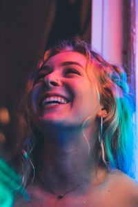 1242x2688 Woman Smiling Near Glass Window 5k