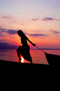 Women Towing Boat Beach Sunset Silhouette